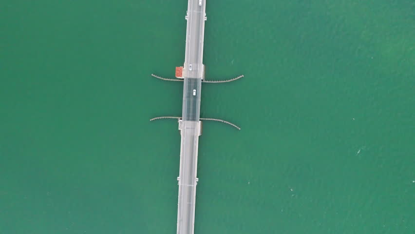 Aerial Above Bridge Road Following White Car Over Green Water in the Florida Keys.