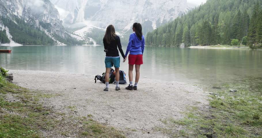 two women hugs and talk looking landscape view at Braies lake. Group of friends summer adventure journey in mountain nature outdoors. Travel exploring Alps, Dolomites, Italy. 4k slow motion 60p video
