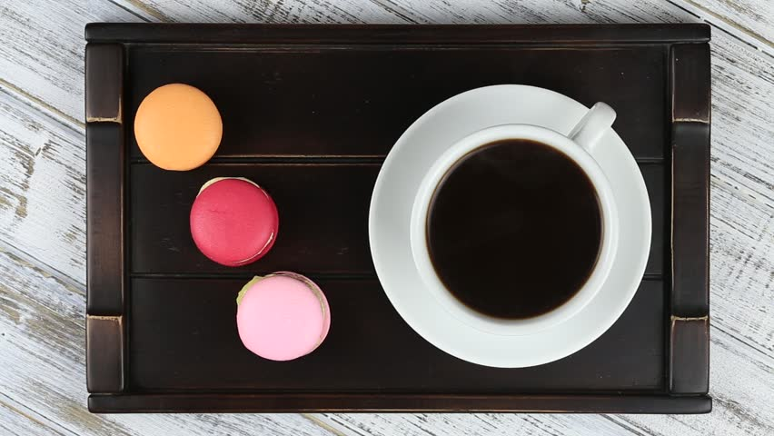 Cup of coffee and macaron cakes on tray on white wooden table. Lifestyle concept. Close up