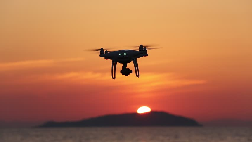 KAGAWA, JAPAN - JUNE 8, 2017: Remote controlled drone Dji Phantom 4 Pro equipped with high resolution video camera flying the sea against a sunset sky.  | Shutterstock HD Video #27636847