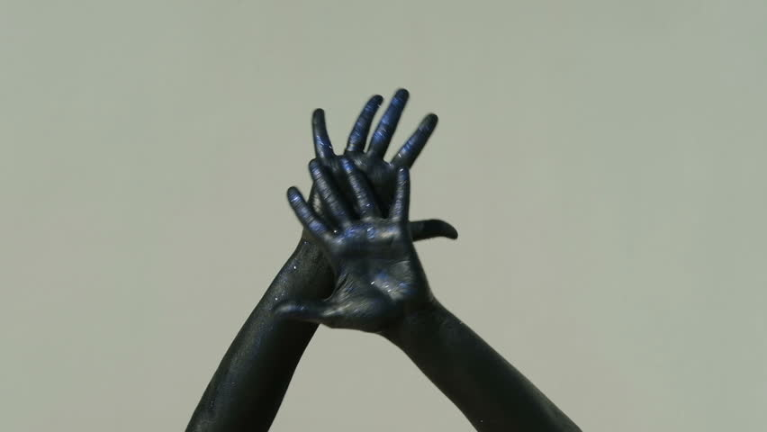 closeup shot of hands covered with black paint bright blue sequins move slowly in dance on gray background. Isolated arms on elbow in frame touch smoothly each other, fingering, showing flexibility of