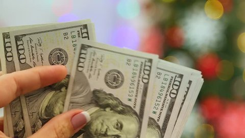 Closeup of female hands holding stack of money in blurry glowing holiday background. Adult woman counting money ready to buy Christmas presents. Real time full hd video footage.