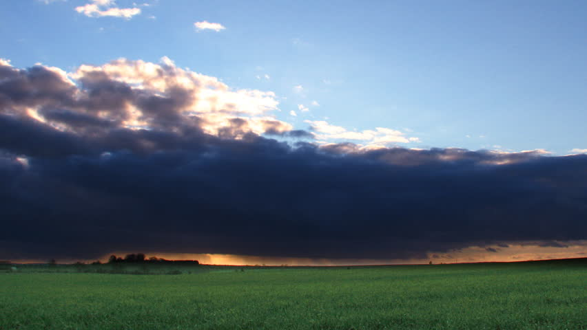 Time lapse sequence of sunset storm clouds passing over fields