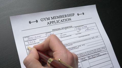 A person filling a gym membership form. Closeup shot.