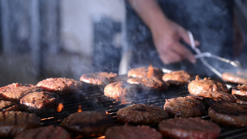 Hamburgers kooking on a barbeque grill with flames and smoke