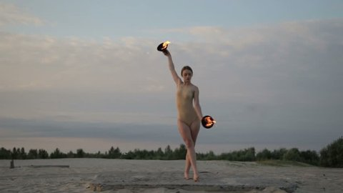 Young beautiful woman is dancing with fire wearing body suit on sunrise in the desert.