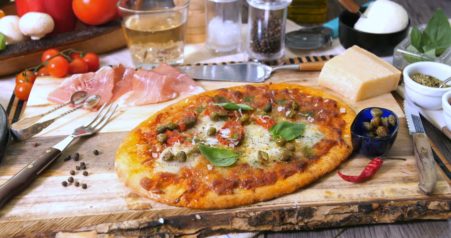 Sprinkling oregano over an Italian pizza margherita | Shutterstock HD Video #27702907