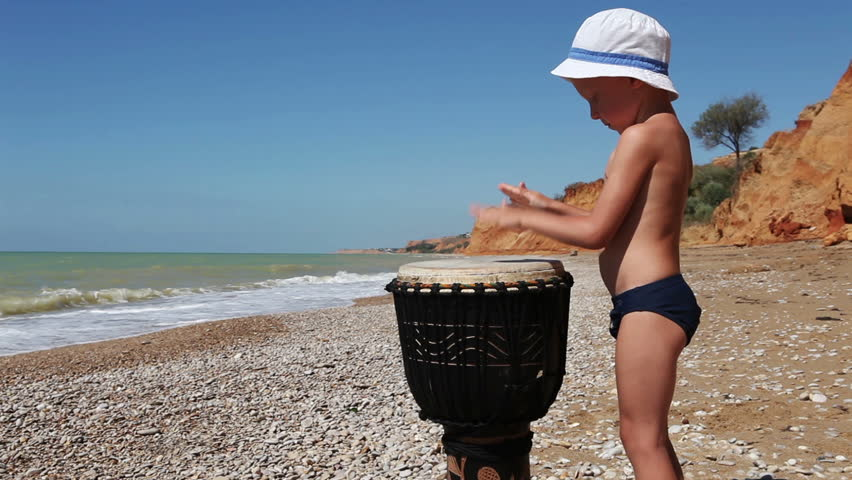 HD Little Boy Playing  African Djembe Drum on the Lonely Wild Beach HD