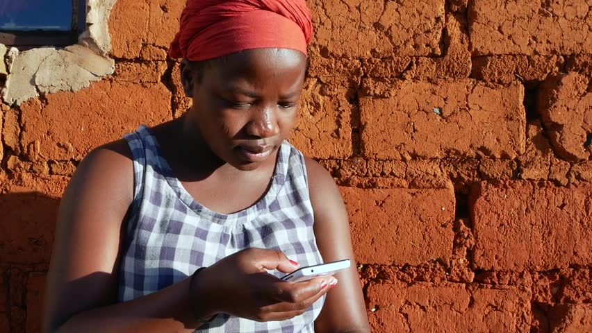 A South African black rural woman sitting down scrolling through her messages on her cell phone mobile telephone - in slow motion.   Shutterstock HD Video #27744877