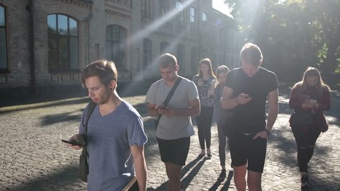 Students busy with smartphones on univesity campus