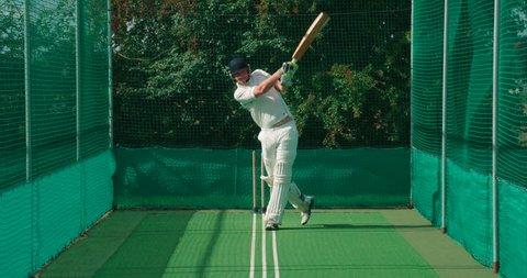A cricket batsman strikes a cricket ball in the nets.