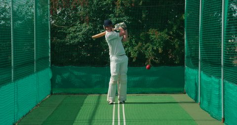 A cricket batsman strikes a cricket ball in the nets.