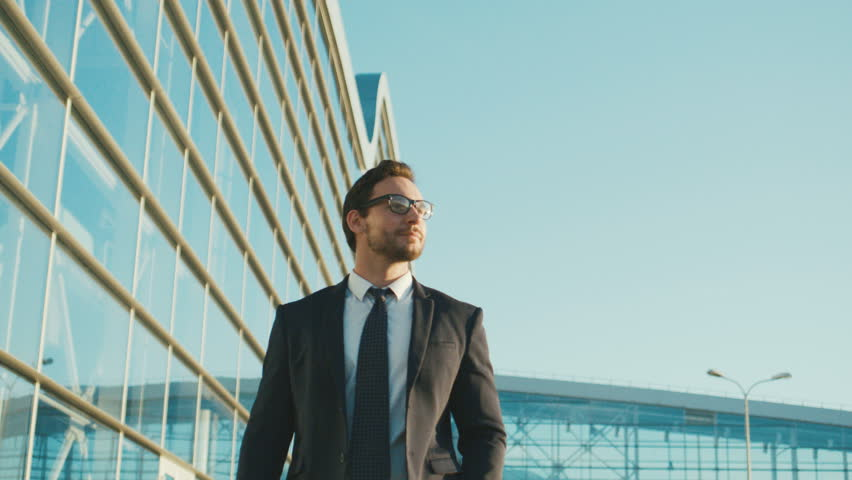 Happy attractive caucasian businessman walking outside near big office building and looking around. Man looking satisfied and happy.