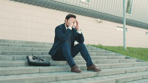 Young businessman sitting on the stairs near office building, feeling bad, sad and annoyed. man tired and having problems, putting hands to the head
