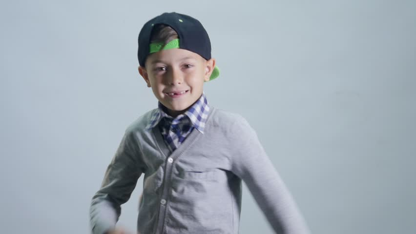 A boy with a toothless smile dances a break with his hands.