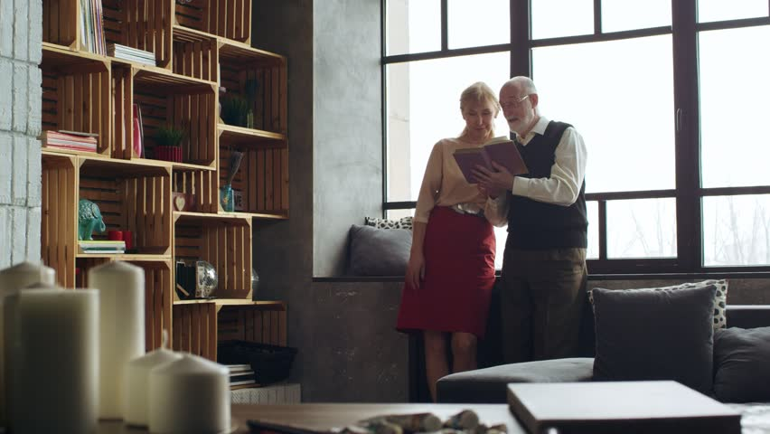 Beautiful elderly elegant couple in a beautiful interior to read the book and spend time together