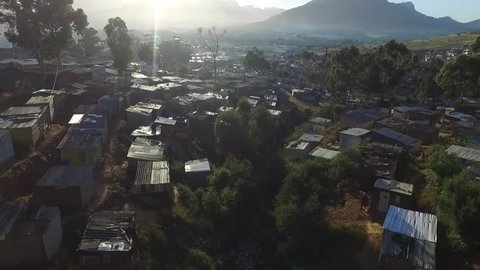 A beautiful, cinematic, aerial view of the sun rising over an african township in Cape Town showing crowded zinc houses with some beautiful flare coming from behind table mountain.