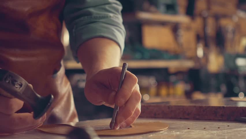 The master makes shoes in the workshop. Press leather with hammer to make holes  | Shutterstock HD Video #27823567