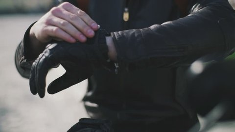 Close up shot of motorcyclist's put on his gloves
