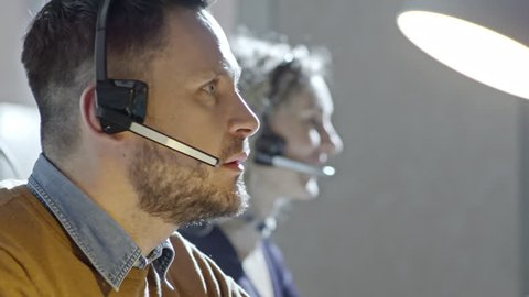 PAN of bearded man with headset talking on voice call with customer in call centre office