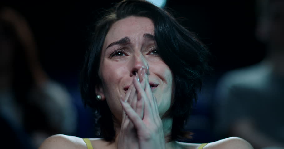 Woman at the cinema beings to cry while watching a sad and emotional movie