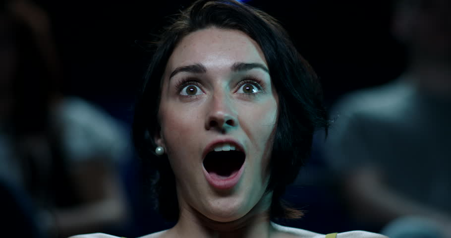 A terrified young woman watches a horror film at the cinema | Shutterstock HD Video #27851029