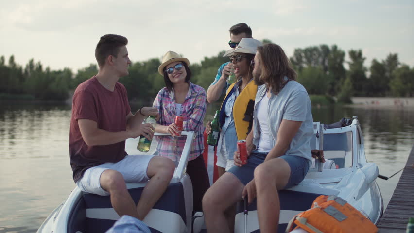 Group of diverse cheerful friends having drinks on pier near boat celebrating Independence day and make self picture with cell phone   Shutterstock HD Video #27852847