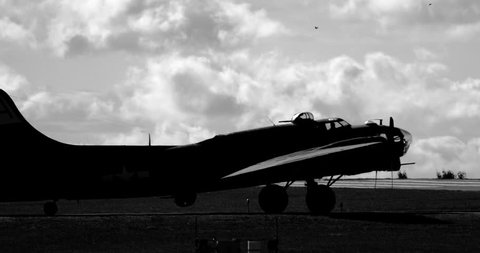 WWII B17 airplane turning on runway - silhouetted in back and white