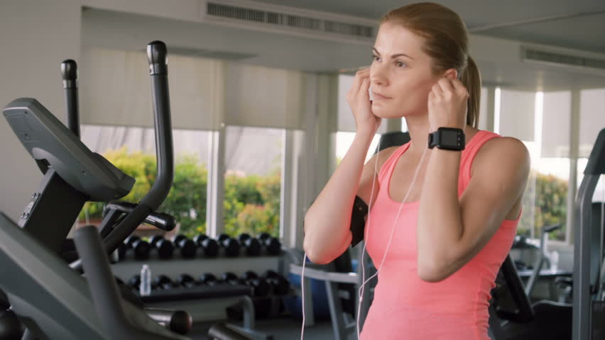 Beautiful fit active sportive young woman in pink t-shirt working out training in gym doing exercises on exercise bicycle. Using her smartwatch, listening music with ear-phones
