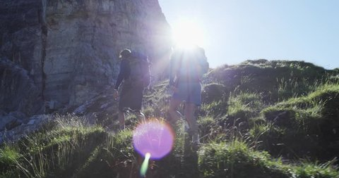 Four friends walking along hiking trail path with sun light flare. Group of friends people summer adventure journey in mountain nature outdoors. Travel exploring Alps. 4k slow motion 60p video