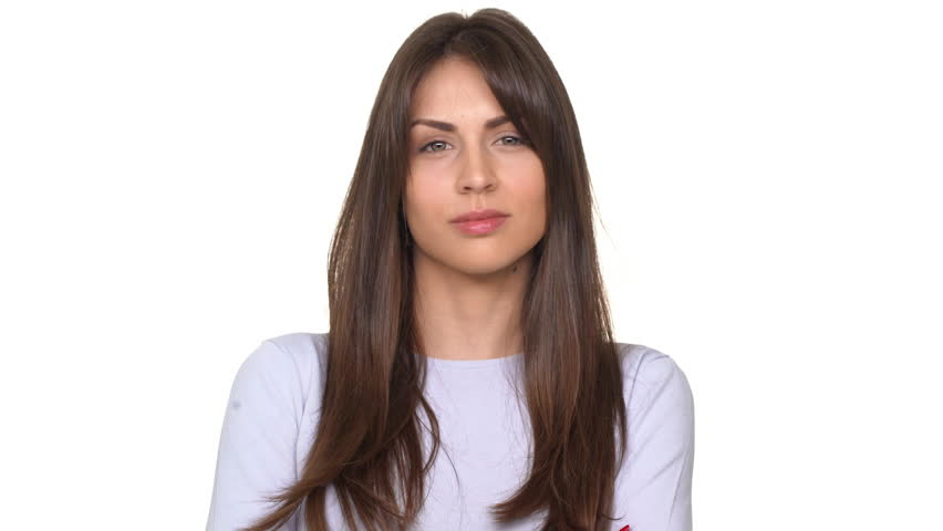Calm young beautiful Caucasian lady with brunette hair saying no and shaking head in disbelief over white background