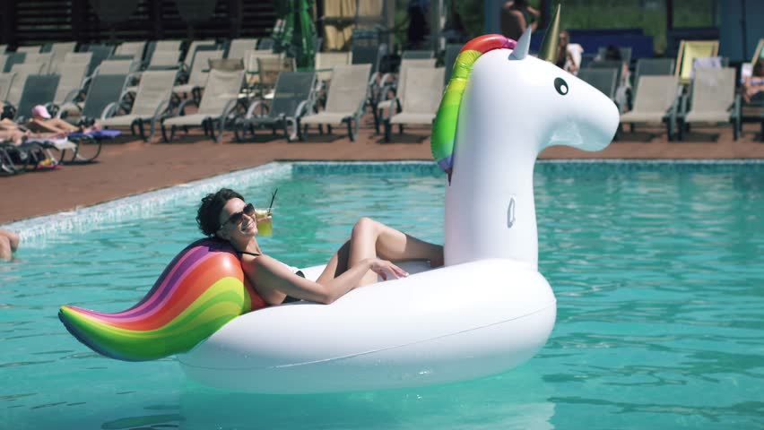 portrait of young sexy woman sunbathing on an inflatable mattress a unicorn in an outdoor pool. beautiful girl in sunglasses drinking a cocktail