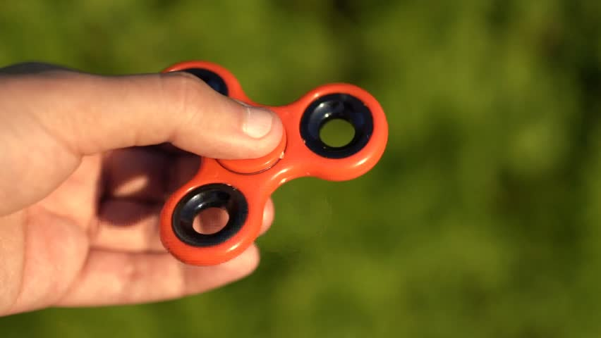 SLOW MOTION: Man playing with fidget spinner. Fidget spinner is a toy which reportedly relieves stress and helps persons with ADD (attention deficit disorder) concentrate more and study better.