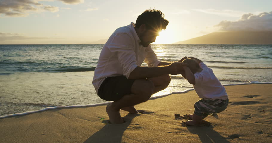 Young dad playing with baby son at the beach at sunset. Baby milestones first steps