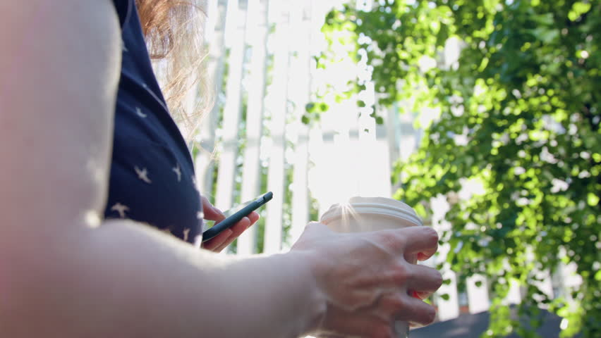 Woman taking a walk in the park using a cellphone and drinking. Close-up shot. Soft focus. | Shutterstock HD Video #27924367