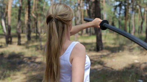 The girl is engaged in ken-jitsu with bokken sword