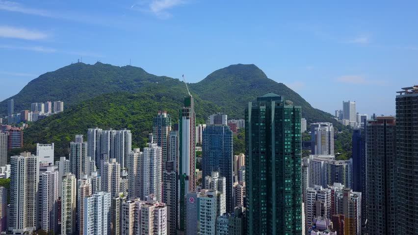 Fly between tall residential towers at dense built Kennedy Town district, Western Hong Kong Island. Construction site ahead, building of new narrow house in progress. Green forested mountains on back