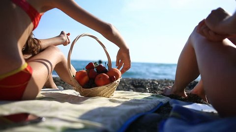 Girl with long hair eating fruit and berries on a crowded sea beach on a background of waves