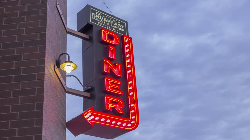 A Medium 4K Timelapse Shot of a Neon Diner Sign Pointing to a Cafe Illuminated Red in front of Beautiful Afternoon Clouds | Shutterstock HD Video #27990277