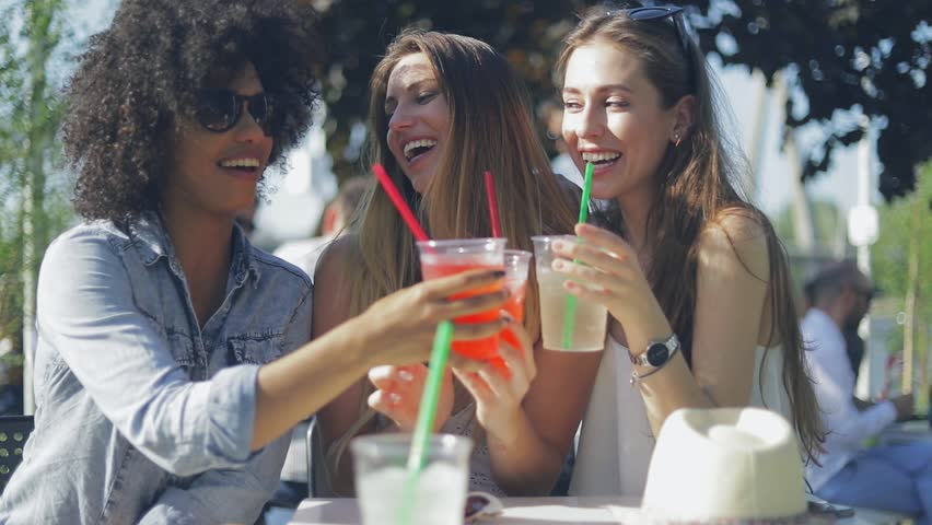 Young Happy Women Wearing Summer Outfits Clinking Glasses With Drinks While Sitting At Table In Outside