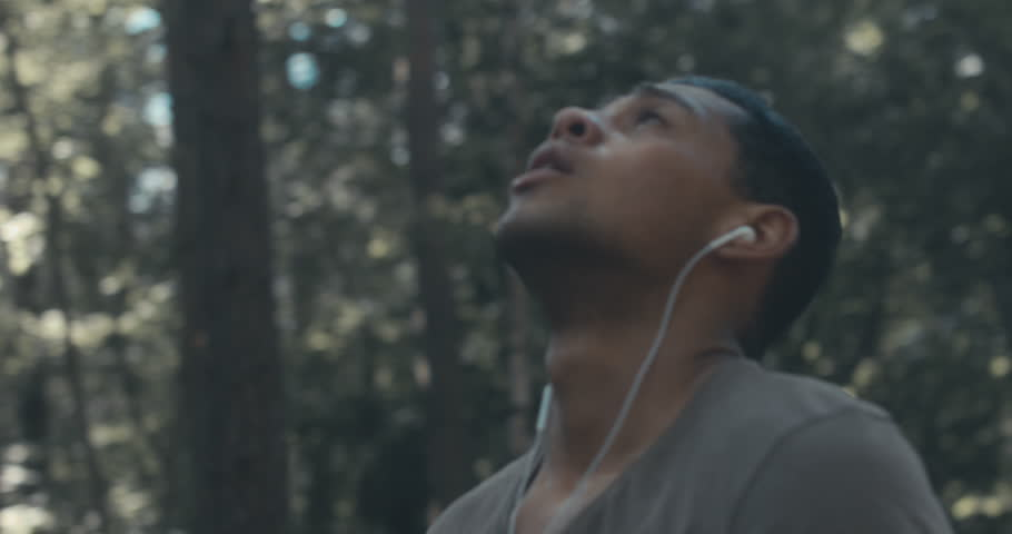 Young fit African American sweating while catching breath after sprinting on the forest road. 4K UHD