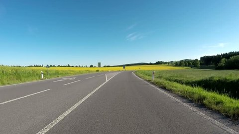 Car drive in evening spring rural countryside road on a sunny day between field and meadow. Landscape with trees and blue sky with sunlight. 60 FPS POV view
