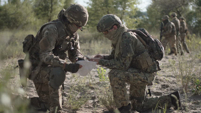 Two soldiers sitting in nature and using map and gps tracker for navigation. Other on background