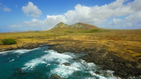 WS AERIAL Rocky coastline with mountain and Moai statues in background / Tapati Rapa Nui, Easter Island, Chile
