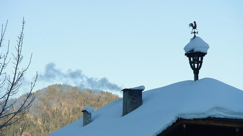MS Weathercock and smoking chimney on snow covered roof with mountain in background / Abtenau, Salzburg state, Austria