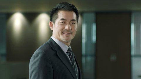successful asian business executive turning to look at camera smiling