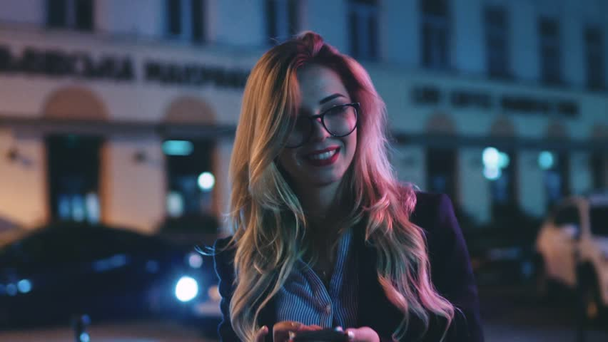Pretty blonde woman with red lipstick, in a business suit walking down the deserted central street at night and using her phone, reacting happily to the message. Modern technologies, successful.