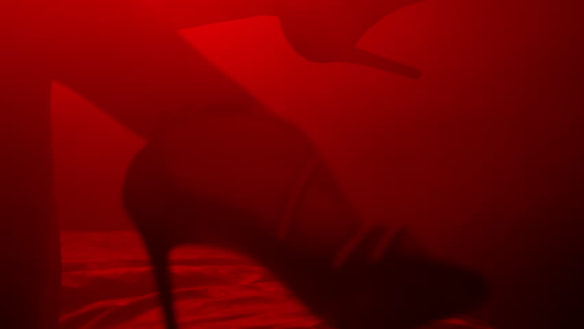 Sexy woman feet in heels shoes. Closeup of sexy female legs in shoes. Erotic concept. Sexy body in red light background