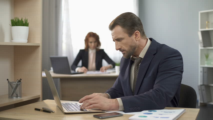 Employee typing on laptop at office desk, answering mobile phone, customer care | Shutterstock HD Video #28054567