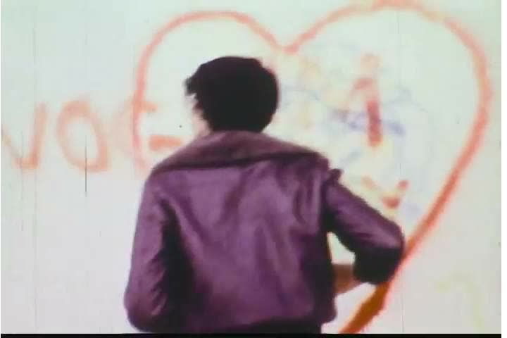1970s: A boy is rejected by a couple, defaces a wall, and is threated by an owner of a building in the 1970s. | Shutterstock HD Video #28062130